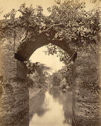 [View though the central arch of a bridge over a canal, Sonargaon?].
